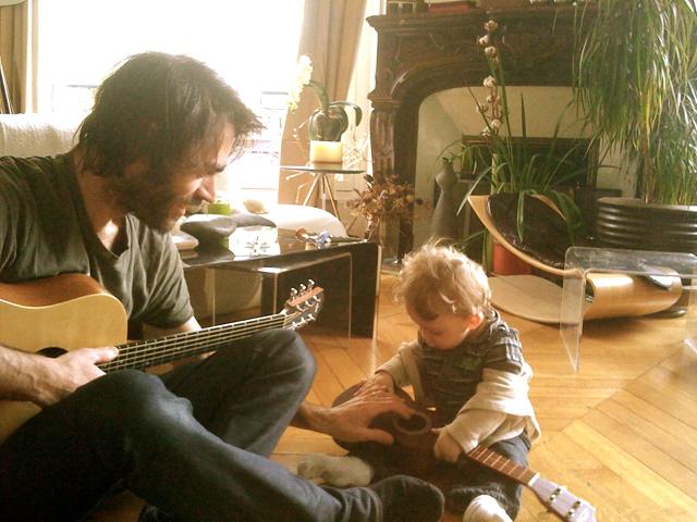 Olivier tocando la guitarra y su hijo