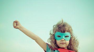 Superhero kid against summer sky background. Girl power and feminism concept