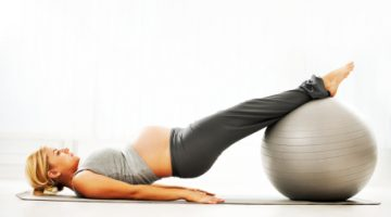 Beautiful blonde pregnant woman exercising with a fitness ball.
