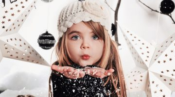 45151055 - a young child is blowing white snowflakes in a studio background scene with stars and christmas ornaments for a holdiay concept.